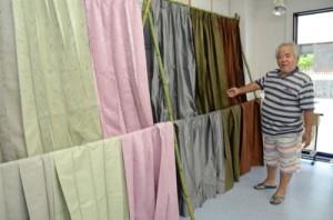 自らが植物で染めた糸で織られた7色のカーテンを紹介する植田正輝さん=20日、奄美市名瀬