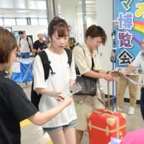 来島者にガイドブックを手渡してシマ博をPRする観光関係者ら=1日、奄美市笠利町