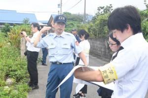 消防職員の案内で火災現場周辺を視察する研究チーム=10日、奄美市笠利町笠利