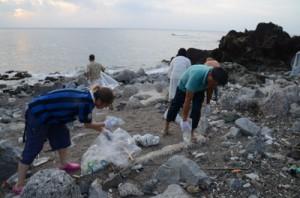 有良の海岸に漂着したペットボトルなどを拾い集める参加者=13日、奄美市名瀬
