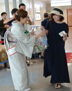 鹿児島へ出発する搭乗客に記念品を贈る関係者=1日、奄美市笠利町