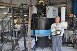 独自開発した機械(写真後ろ)で、廃品ダンボールをリサイクルして作った商品を手にする福社長=22日、知名町