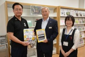 スポンサー制度で提供された雑誌を手にする(左から)町田酒造㈱の中村社長と碇山教育長=9日、龍郷町