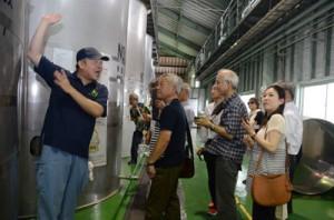 宇検村の奄美大島開運酒造の工場見学で、音響熟成の説明に聞き入る参加者ら=6日、宇検村