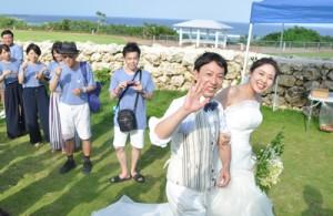 沖永良部島の海が見える場所で念願の結婚式を挙げ、笑顔を見せる大橋敏之さんと千葉里さん=14日、和泊町