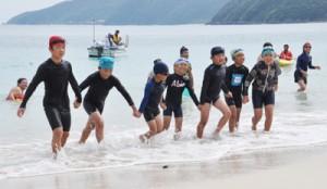 1.3キロを泳ぎきってゴールへ走る児童=7日、奄美市名瀬