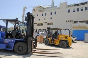 大量の生活物資が届き、荷役に追われる作業員=12日、沖永良部島の伊延港
