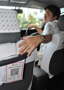 助手席の後ろに貼られたQRコードをスマホで読み取って決済できるようになった南陸運のタクシー=5日、与論町