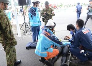 救助者のトリアージを行いながら情報交換する消防、陸自、県立大島病院関係者=25日、奄美市名瀬