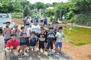 坂口さん(左下)からトウギョの稚魚を受け取った地元の子どもたち=27日、知名町瀬利覚