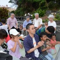 墓前で手を合わせる親子と一重一瓶を囲んで先祖の霊を送る一族=15日、徳之島町亀津