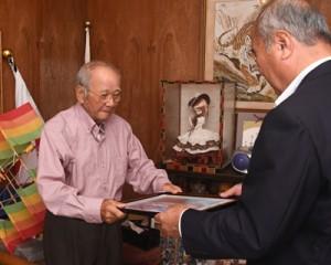 米寿の記念写真を受け取る照幸喜さん(左)=8日、奄美市笠利町喜瀬