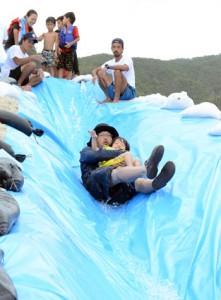 滑り台を楽しむ親子連れ=11日、国直海岸
