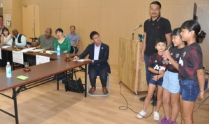 地元の子どもたち(右)の事例発表に耳を傾けるドミニカ国、グレナダの関係者ら=27日、和泊町役場