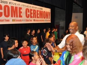 カリブ3カ国の関係者とダンスで交流した後、ハイタッチする地元の子どもたち=26日、知名町