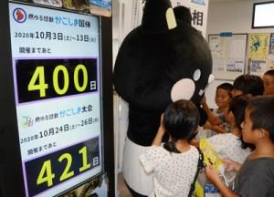 かごしま国体開幕までの残り日数を示すボードの横で、大会のPR活動をするコクトくん=30日、奄美市笠利町