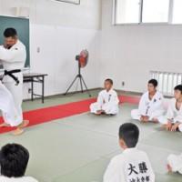子どもたちに柔道を教える鈴木さん(左)=19日、和泊町