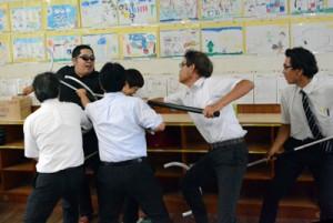訓練で協力して不審者役を取り押さえる教諭ら=9日、名瀬小学校