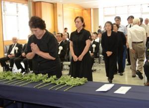 手を合わせて犠牲者の冥福を祈る参列者=15日、奄美市名瀬