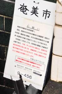 永田墓地の利用者の登録申請を呼び掛ける立て札=11日、奄美市名瀬