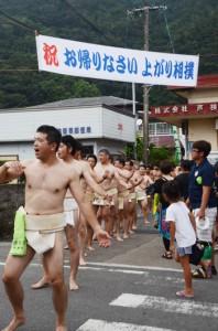 「上がり相撲」に参加するために帰省する集落出身者を歓迎する横断幕と、「振り出し」で土俵入りする力士たち=17日、宇検村芦検