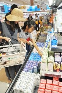 品薄が続いていた牛乳などの商品を手に取る買い物客=17日、和泊町のAコープ和泊店