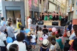 フラダンスなどが披露され、人垣ができた特設舞台=10日、奄美市名瀬