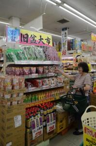 グリーンストア入舟店で、お盆特集コーナーの商品を手にする買い物客=8日、奄美市名瀬