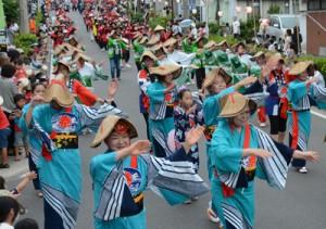 踊り連がにぎやかに通りを練り歩いたあまぎ祭のパレード=18日、天城町平土野