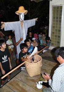 福の神「イッサンボー」を振りかざしながら家回りをした「イッサンサン」=27日夜、伊仙町犬田布
