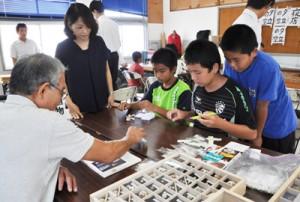 講師と一緒に貝の名前を確認する児童生徒=22日、奄美市笠利町