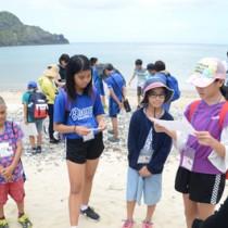 多くの対馬丸犠牲者が漂着した宇検村宇検の船越浜で、生存者の証言を音読する参加者ら=24日、宇検村