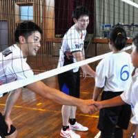 ミニゲーム後、子どもたちと握手を交わす本間選手(左)と浅野選手=17日、和泊町