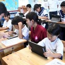 タブレットを操作し、eラーニング教材「すらら」で学習する手々小中学校の児童生徒ら=21日、徳之島町手々