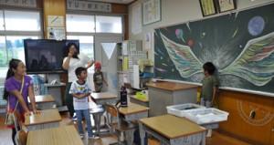 黒板アートの前で記念に撮影してもらう児童=1日、龍郷町の秋名小学校