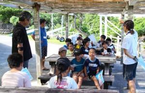 野外学習で海の生態について学ぶ児童ら(提供写真)=6日、与論町