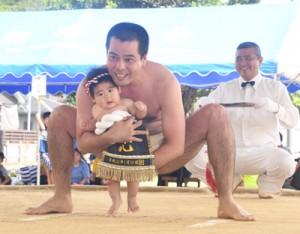 新生児の土俵入りもあった大熊町内会の敬老会・豊年相撲=8日、奄美市名瀬