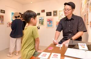 似顔絵を通じてイラストの面白さを伝える竹添さん=8月25日 東京・国立市