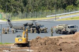 日米合同訓練で、陸自奄美駐屯地に着陸した米陸軍のブラックホークと米兵たち=16日、奄美市