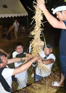 力を合わせてわらを編み上げた伝統の綱かき=8日夜、伊仙町伊仙
