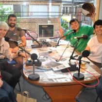 ラジオ番組収録後、笑顔を見せるミルズさん(左から2人目)と、武さん(左)、田中さん(右)=27日、奄美市名瀬