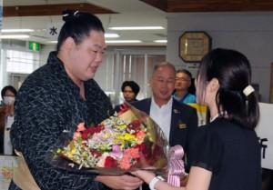 役場職員らの歓迎を受け、笑顔で花束を受け取る明生関(左)=25日、瀬戸内町役場