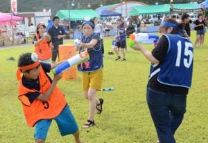 チーム対抗で必死に水を掛け合う水てっぽう合戦参加者=1日、奄美市住用町