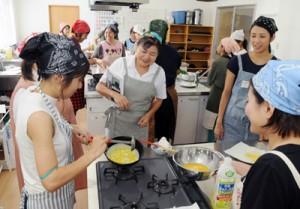 福田さん(中央)の指導で料理に取り組む参加者=23日、瀬戸内町