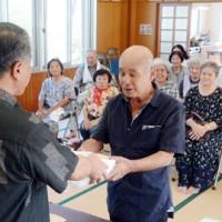 伊集院村長(左)から敬老年金が贈られた支給式=13日、大和村大棚公民館
