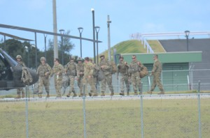 米陸軍のヘリ「ブラックホーク」に乗り込み、撤収する米兵たち=24日、奄美市名瀬