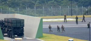 奄美駐屯地のグラウンドで03式中距離地対空誘導ミサイルの発射装置の方向へ小銃を抱えて走る米兵たち=18日、奄美市名瀬