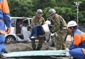 陸自と消防などで連携を確認した救出・救護訓練=1日、瀬戸内町の古仁屋小学校グラウンド