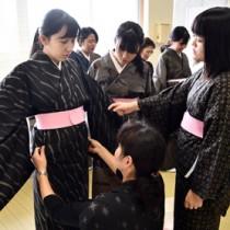 紬協組青年部の指導で着付けに挑戦する生徒たち。着用体験のある生徒は大島紬への関心が高かった=2018年12月4日、古仁屋高校