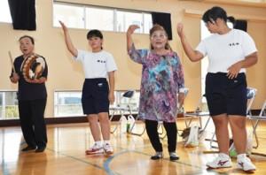 地域住民を講師に八月踊りを練習する生徒=17日、龍郷町